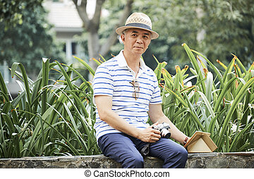 Positive senior man resting in park
