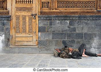 Homeless man in India sleeping on the street.