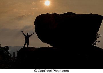 Praying man silhouette on sunset background