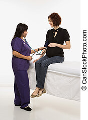 Pregnant Caucasian mid-adult woman having vital signs checked by nurse.