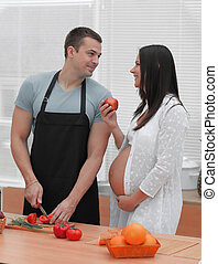 Pregnant woman with husband cooking food in kitchen