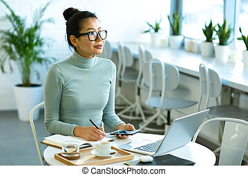 Pretty Asian student in eyeglasses sitting by table in front of laptop in cafe