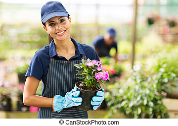 female nursery owner with pot of flowers
