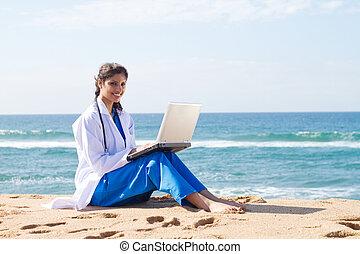 pretty indian intern using laptop on beach