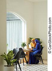 Pretty muslim women with digital tablet