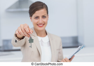 Pretty real estate agent giving house key