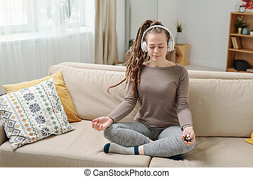 Pretty relaxed girl with antistress balls sitting in pose of lotus on couch