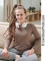 Pretty smiling girl in activewear and headphones sitting on couch at home