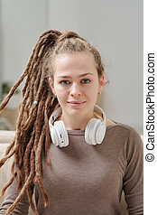 Pretty smiling girl in pullover with headphones around her neck