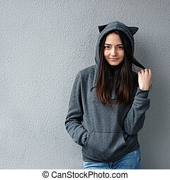 Pretty teenage girl standing against wall
