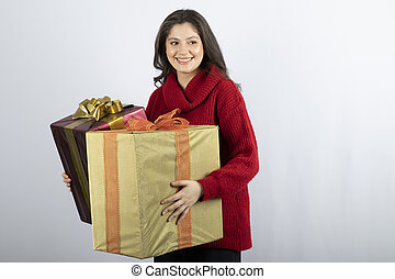 Pretty woman in red sweater holding Christmas presents