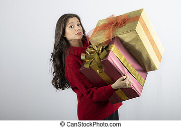 Pretty woman in red sweater holding two boxes of Christmas presents
