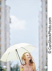 Pretty woman walking with umbrella