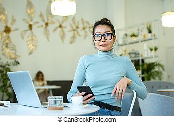 Pretty young casual woman with smartphone looking at you while sitting by table