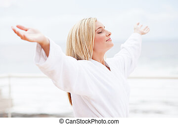 pretty young woman in bathrobe with arms open