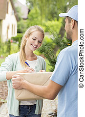 Professional courier with happy young customer signing a delivery form