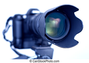 Professional digital SLR camera with telephoto zoom lens on tripod. Isolated white background, focus on lens hood.