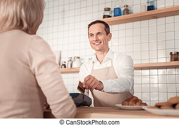 Professional nice cashier taking payment