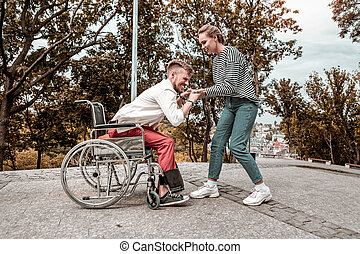 Professional social worker smiling and helping disabled man to stand up