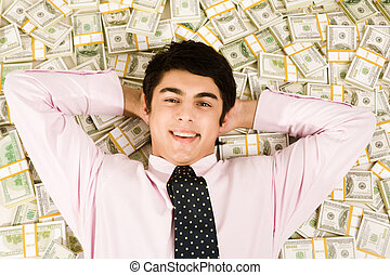 Image of happy businessman lying on heap of dollars and smiling