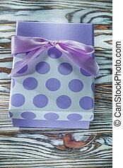 Purple present box on vintage wooden board