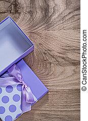 Purple present box on wooden board top view celebrations concept