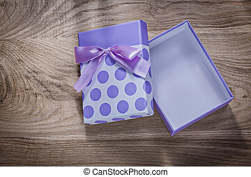 Purple present box with tape on wooden board celebrations concep