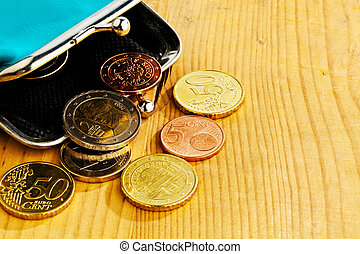coins and an empty wallet with a few €. photo icon on debt and poverty