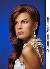 Portrait of young woman with pearls necklace with stylish hairdo