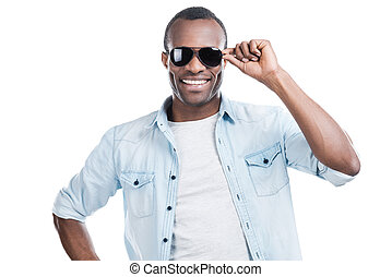 Ready for winning hearts. Handsome young black man adjusting his sunglasses and smiling at camera while standing against white background