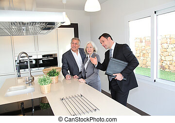 Real-estate agent showing interior of house to senior couple