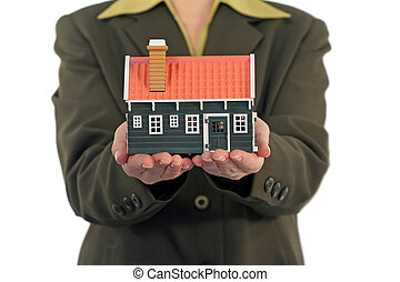 Real estate business woman offering a housing solution - isolated (shallow DOF, focud on the house and hands)