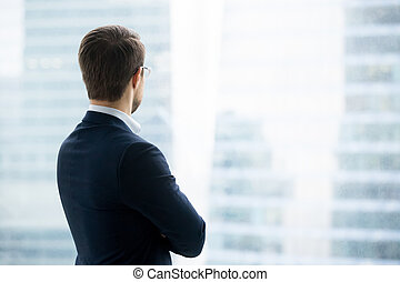 Rear view of businessman in suit standing looking through window