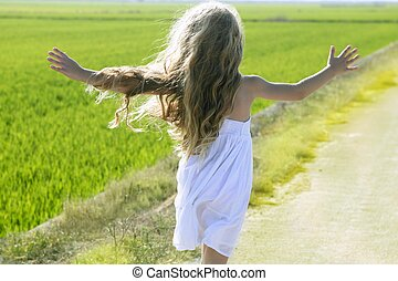 rear view running open arms little girl in meadow track