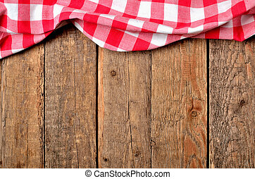 Red checkered tablecloth top frame on vintage wooden table background - view from above
