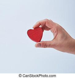 red heart in a human hand on a white background