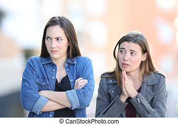 Regretful girl asking forgiveness to her angry friend