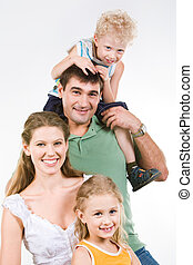 Portrait of boy sitting on neck of father with mother and sister near by