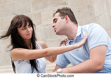 Young couple having relationship problems - woman refuses kissing from man