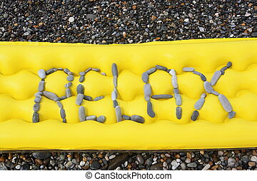 relax message from pebbles on a air-bed. air-bed is laying on a sea coast
