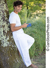 relaxed man reading book in nature