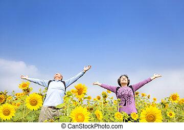 relaxed senior couple standing in the sunflower garden