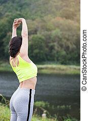 Relaxed woman breathing fresh air raising arms.