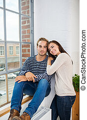 Relaxed young couple sitting in font of a window