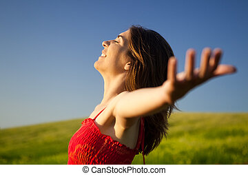 Portrait of beautiful young woman relaxing on the field with both arms open