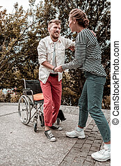 Reliable social worker helping her disabled patient to stand up