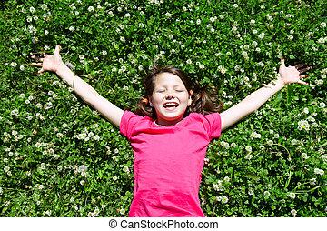 Portrait of a joyful little girl lying on grass