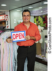 retail business: proud store owner with open sign