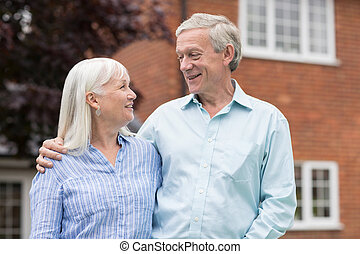 Retired Couple Standing Outside Home