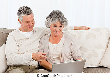 Retired lovers looking at their laptop